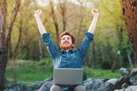 Happy cheerful hipster man with a laptop sitting outdoors in nature, freedom and happiness concept Stockfoto