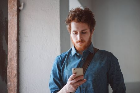 Hipster young man having a walk and texting with his mobile phone Stockfoto