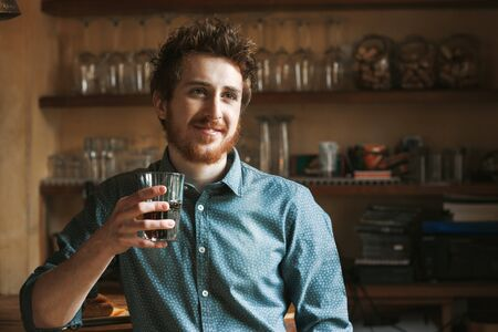 Hipster young man smiling and drinking a glass of coke with bar wooden shelves on background