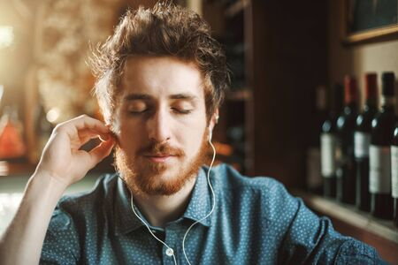Young hipster man sitting at bar table and listening to music using earphones, he is smiling at camera