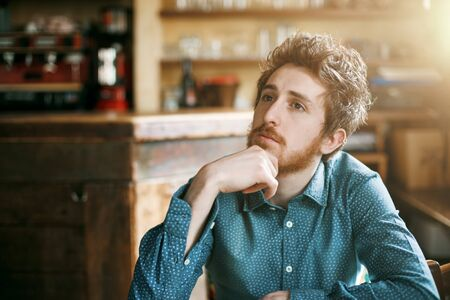 Young pensive hipster posing with hand on chin looking away