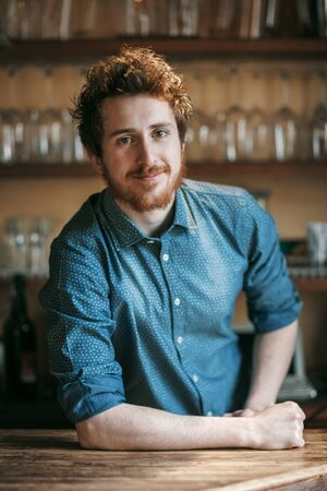 Young barman leaning on wooden bar counter and smiling at camera, shelves with glasses on background Stockfoto