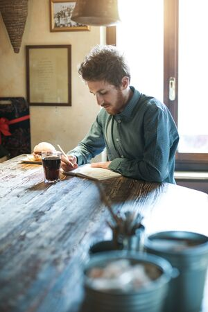 Young hipster man sketching on a notebook in his studio on a rustic wooden table Stockfoto