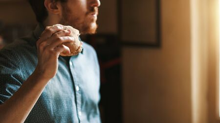 Hungry young hipster man eating a tasty sandwich with ham, hand close up Stockfoto - 146851533