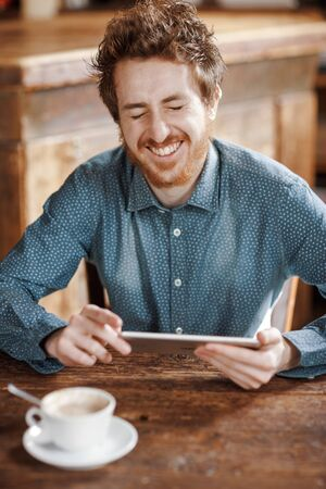 Cheerful hipster enjoying and social networking with his tablet during a coffee break Stockfoto - 146851535