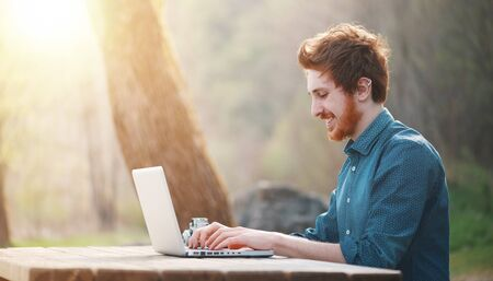 Young smiling hipster man relaxing and having a break at the park and using a laptop Stockfoto - 146851558