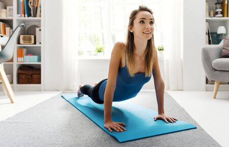 Young woman exercising in her living room at home, she is doing pilates push ups on a mat