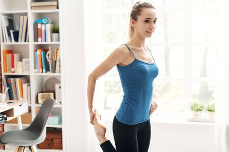 Young woman exercising at home in the living room, she is stretching her leg, fitness and wellness concept 版權商用圖片