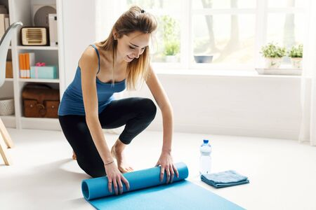 Young smiling woman rolling her yoga mat after exercising and doing meditation at home