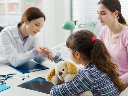 Pediatrician visiting a young patient with broken wrist and bandage, the girl is holding her teddy bear 版權商用圖片