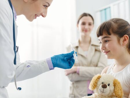 Friendly female doctor showing the syringe to a girl before giving the injection, the girl is relaxed and smiling