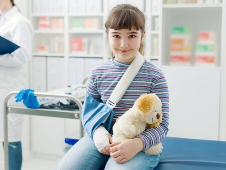 Cute smiling girl with her teddy bear sitting on the examination couch in the doctor's office, her mother and the doctor are talking in the background Imagens