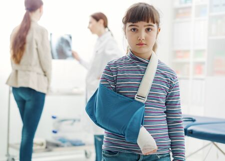 Cute sad girl with broken arm in the doctor's office, she is wearing an arm brace and looking at camera