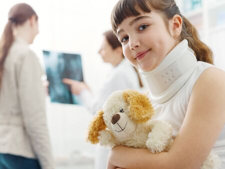 Girl with cervical collar in the doctor's office, she is smiling and holding her teddy bear