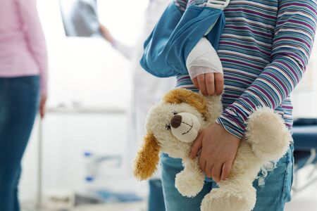 Cute girl with arm brace in the doctor's office, she is holding a teddy bear plushie, children and healthcare concept Stockfoto - 147887421