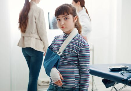 Cute sad girl with broken arm in the doctor's office, she is wearing an arm brace and looking at camera Stockfoto - 147887422