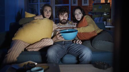 Friends sitting on the sofa at home and watching scary horror movie together, entertainment concept Stockfoto - 147887423