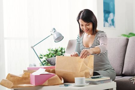 Happy excited woman at home, she has received a postal parcel and she is unboxing her gift, delivery and online shopping concept Stockfoto - 147887426