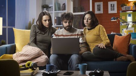 Friends sitting on the couch at home and watching suspense movies online