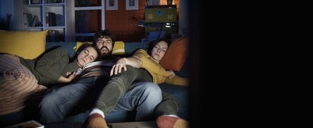 Friends falling asleep on the sofa at home while watching TV at night Stockfoto - 147887432