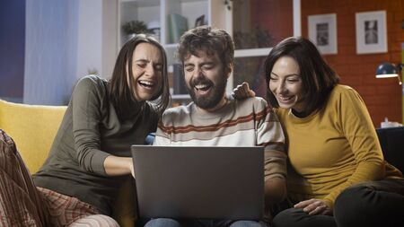 Cheerful friends sitting on the sofa at home and connecting online with their laptop, they are social networking and having fun Stockfoto - 147887434