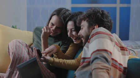 Happy friends sitting on the sofa at home and social networking with their smartphone, togetherness and technology concept Stockfoto - 147887445