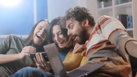 Happy friends sitting on the sofa at home and social networking with their smartphone, togetherness and technology concept