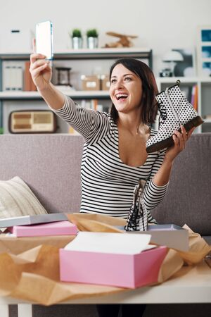 Fashion blogger at home taking a selfie with her new purchases after unboxing a postal parcel