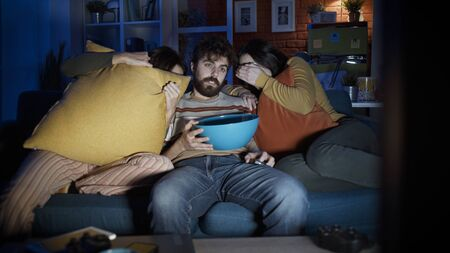 Friends sitting on the sofa at home and watching scary horror movie together, entertainment concept Stockfoto - 147887448