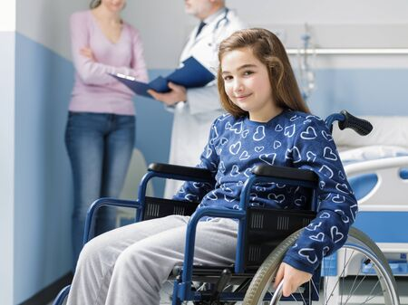 Smiling girl in wheelchair at the hospital, her mother and the doctor are talking in the background Stockfoto - 147887451