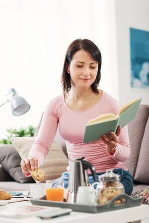 Serene relaxed woman having breakfast in the morning, she is sitting on the couch and reading a book 版權商用圖片