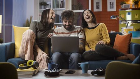 Cheerful friends sitting on the sofa at home and connecting online with their laptop, they are social networking and having fun Stockfoto - 147887452