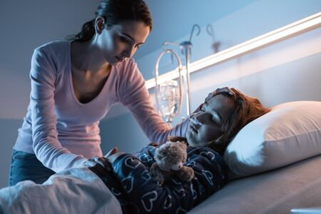 Young mother assisting her young child lying in a hospital bed at night, she is worried and caressing her head Stockfoto - 147887453
