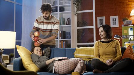 Young friends spending time together at home, the man is stacking apples on his friends head while she is lying on the sofa