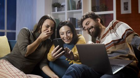 Friends sitting on the sofa at home and social networking with a smartphone, they are laughing and watching videos together 版權商用圖片 - 147887616