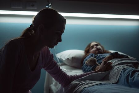 Desperate young mother assisting her sick child lying in a hospital bed at night
