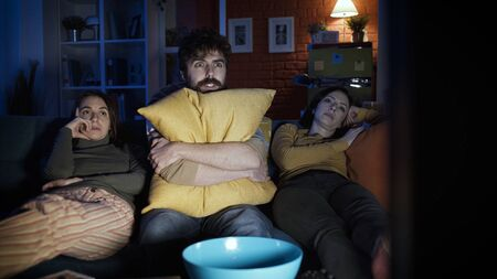 Friends sitting on the sofa at home and watching scary horror movie together, entertainment concept Stockfoto - 147887622