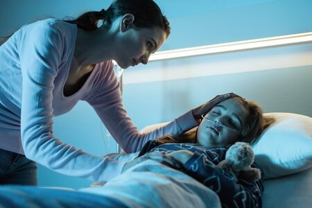 Young mother assisting her young child lying in a hospital bed at night, she is worried and caressing her head