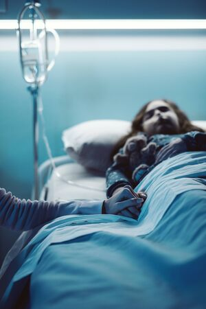 Woman assisting her sick child lying in bed at the hospital at night, she is holding her hand Stockfoto