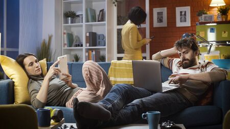 Friends connecting with their devices at home and ignoring each other, technology and lifestyle concept