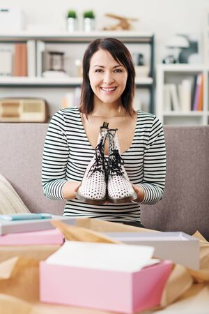Cheerful young woman at home receiving a parcel with fashion shoes inside, online shopping and delivery concept 版權商用圖片 - 147887628