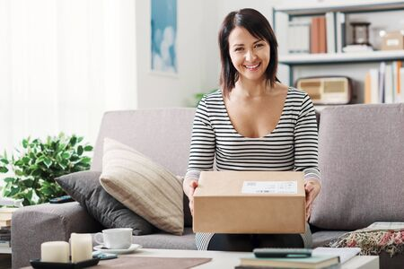 Smiling young woman at home on the couch, she has received a postal parcel, online shopping and delivery concept Stockfoto