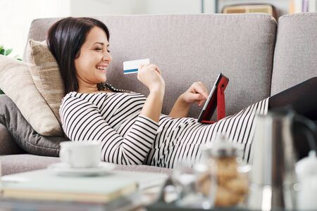 Happy woman shopping online at home using a digital tablet, she is holding her credit card Stockfoto - 147887634