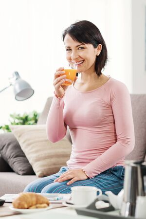 Serene smiling woman having breakfast in the morning, she is sitting on the couch and drinking orange juice 版權商用圖片