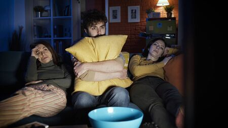 Friends sitting on the sofa at home and watching scary horror movie together, entertainment concept