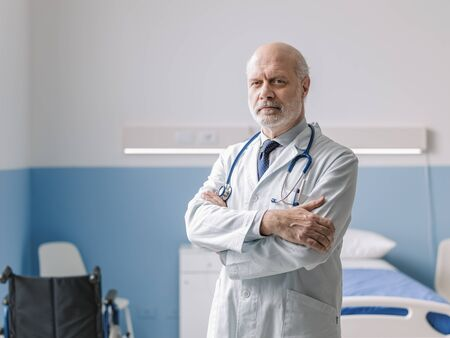 Professional doctor standing next to a hospital bed and posing with folded arms, healthcare professionals and medicine concept Stockfoto - 147887638