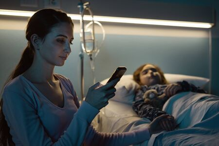 Young woman assisting her child at hospital at night, she is chatting with her smartphone and connecting online Stockfoto