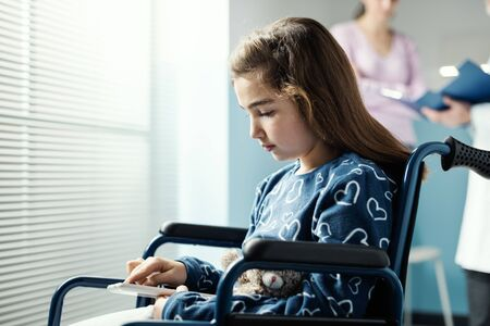 Cute girl in wheelchair at the hospital using a tablet, her mother and the doctor are talking in the background Stockfoto - 147427258