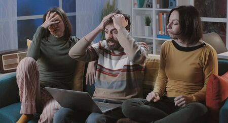 Disappointed young friends watching sports online, they are angry and frustrated