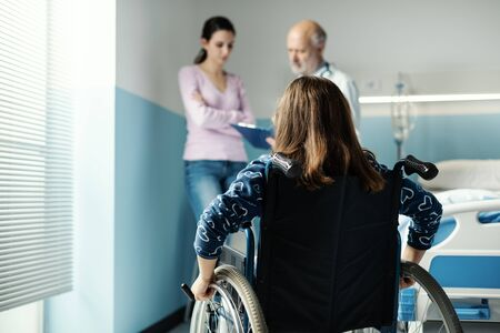 Girl in wheelchair at the hospital, her mother and the doctor are discussing about her health